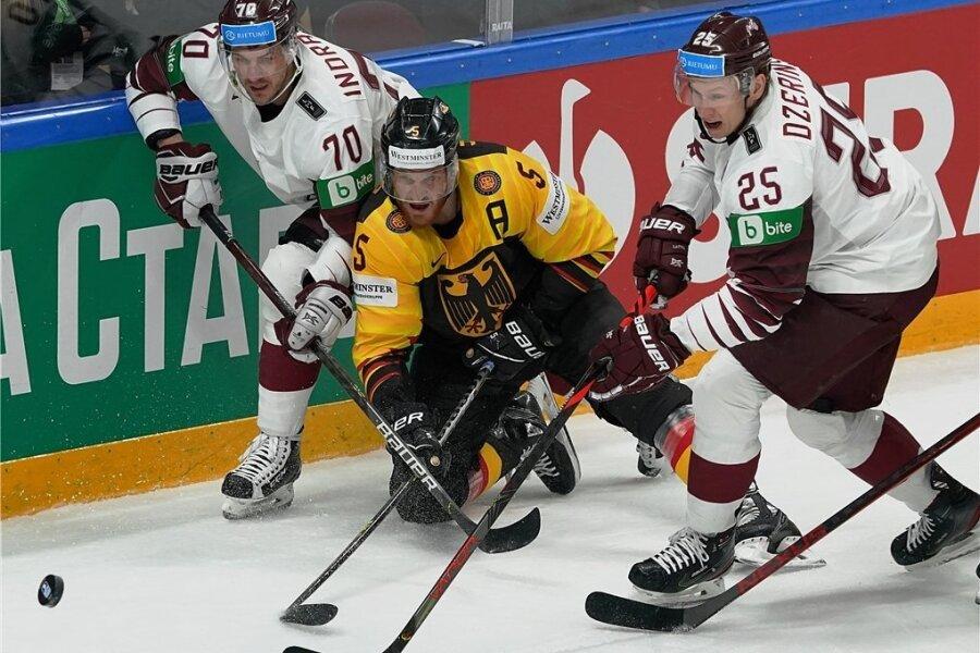 Korbinian Holzer (M.), der zum Abschluss der WM in das Allstar-Team gewählt wurde, versucht sich in dieser Szene gegen Lettlands Miks Indrasis und Andris Dzerins durchzusetzen. Foto: Roman Koksarov/dpa