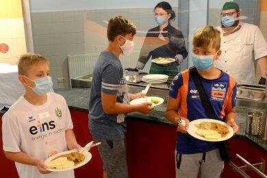 Auch an der Essenausgabe gelten Hygienevorschriften: Jason, Max und Finnley holen sich mit Maske ihr Mittagessen, das hinter der Plexiglas-Scheibe von Silvana Opel und Kevin Troschke ausgegeben wird.