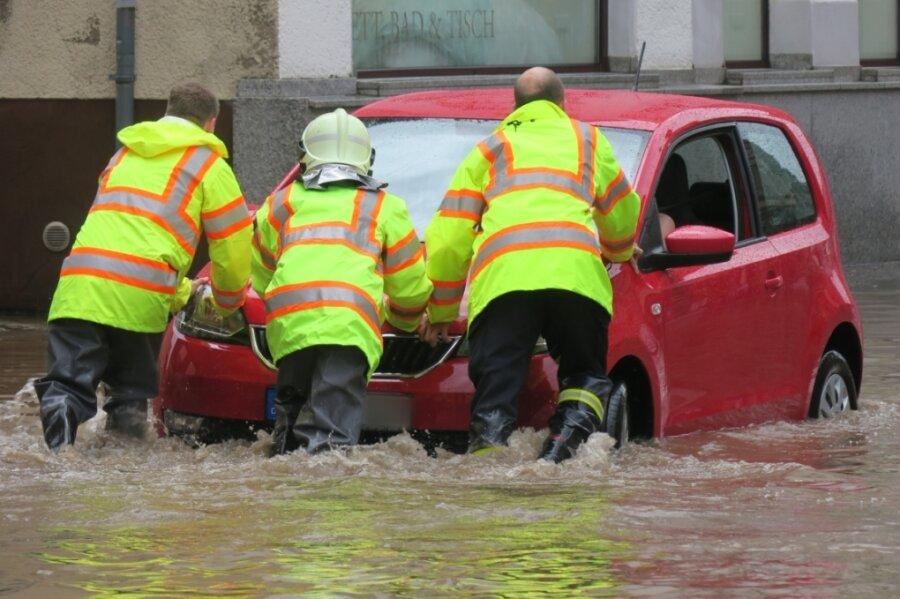 Nach dem Unwetter steckte ein Fahrzeug in den Fluten auf der Auer Bahnhofstraße fest. Rettungskräfte der Feuerwehr schoben das Auto aus dem Wasser.