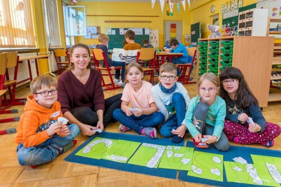 So sieht das Puzzle aus, mit dessen Hilfe Grundschullehrerin Julia Kluge (2. v. l.) ihren Erstklässlern Nils Meyer, Luna Sachse, Emil Melzer, Klara Wappler und Elena Uhlig (v. l.) das Alphabet erklärt.