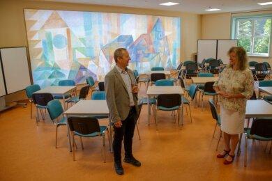 Bürgermeister Sebastian Nestler und Schulleiterin Katrin Becher im neu gestalten Mehrzweckraum mit beleuchtetem Wandbild.