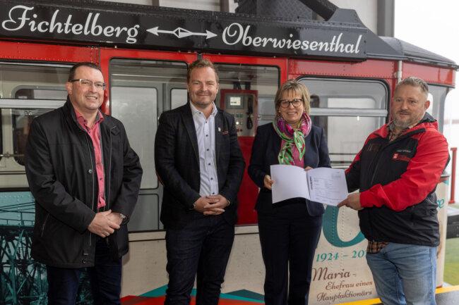 Sachsens Tourismusministerin Barbara Klepsch hat am Mittwochvormittag auf dem Fichtelberg in Oberwiesenthal einen Förderbescheid in Höhe von 202.000 EUR an René Lötzsch (r.) als Geschäftsführer der Fichtelberg Schwebebahn GmbH überreicht.