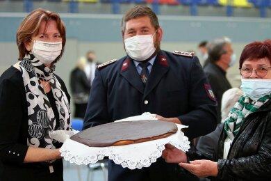OB Heidrun Hiemer (l.) liebt Schokoladenkuchen aus Crandorf. Deshalb lagen Erla-Crandorfs Ortsvorsteherin Gisela Schmidt und der stellvertretende Ortswehrleiter Christian Tittes mit dem Geschenk völlig richtig.