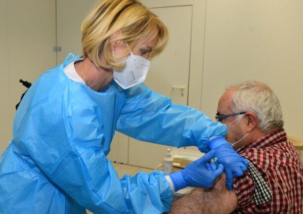 Schwester Anke impft im Impfzentrum für Mittelsachsen im Simmelcenter in Mittweida einen älteren Patienten.