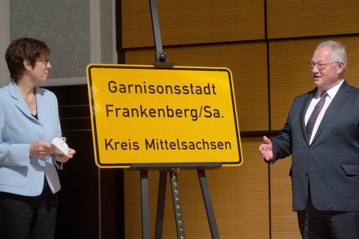 """Bundesverteidigungsministerin Annegret Kramp-Karrenbauer und Frankenbergs Bürgermeister Thomas Firmenich enthüllen im Beisein des Sachsen-Ministerpräsidenten Michael Kretschmer ein Ortseingangsschild der Stadt. Diese trägt nun die Bezeichnung """"Garnisonsstadt""""."""