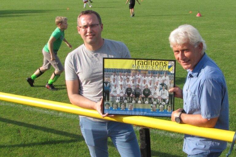 Heiko Blochwitz (l.) und Mike Leye zeigen ein Foto der Traditionsmannschaft des FC Carl Zeiss Jena, der Wolfgang Blochwitz lange Zeit angehörte.