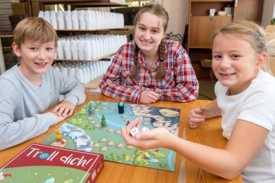 Zwei Würfel und los geht's: Raphaela Haude (Mitte) sowie Felix und Laura Franke probierten das erste fertiggestellte Spiel gleich in der Seiffener Werkstatt von Tino Günther aus.