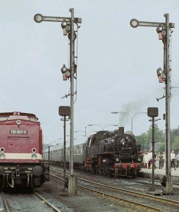 """Am 16. Juni 1974 stehen im Bahnhof Aue zur Abfahrt bereit: Links der Personenzug nach Adorf, rechts ein Zug zum """"Tag des Eisenbahners""""."""