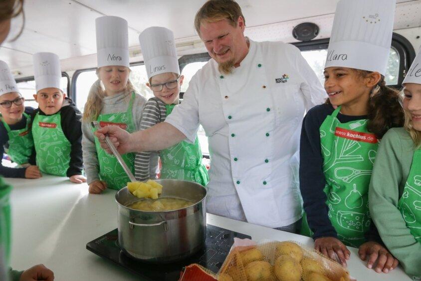 In einem sogenannten Kochbus zeigt Koch Martin Schneider den Niederfrohnaer Schülern, wie vielfältig die Kartoffel zubereitet werden kann. Dabei wurden die Kinder selbst aktiv, schälten und schnitten die Knollen.