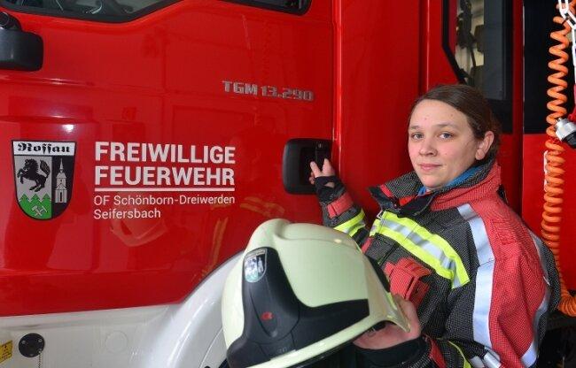 Jennifer Gräfe-Müller steht mit ihrer Ausrüstung am Feuerwehrauto im Gerätehaus in Seifersbach.
