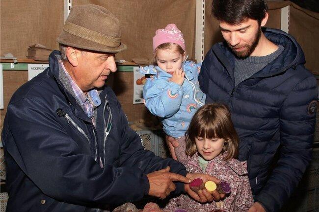 So farbenfroh kann Kartoffelgenuss sein: Ulrich Gündel (links) zeigt Florian Preuß und den Kindern Nora und Thea, wie man Abwechslung auf den Teller bringt.