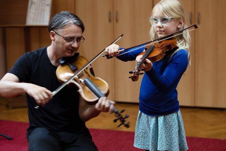 Die siebenjährige Edith aus Plauen probierte am Samstag hoch konzentriert eine Kindergeige aus. Musikpädagoge Torsten Trommer zeigte sanft, wie die Saiten gestrichen werden.
