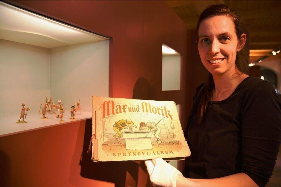 Museumsleiterin Tina Reitz zeigt ein historisches Sammelbilder-Album zu Max und Moritz. Es ist in der Sonderausstellung über Wilhelm Busch zu sehen.