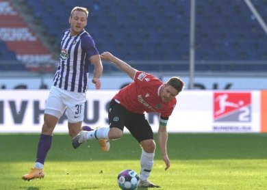 Hannovers Dominik Kaiser (r) und Ben Zolinski von Erzgebirge Aue kämpfen um den Ball.