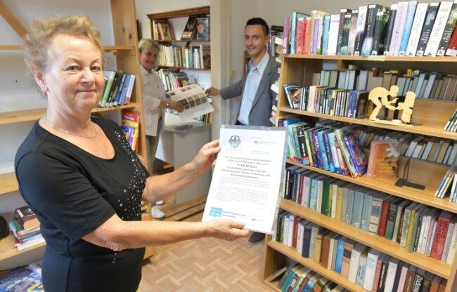 Bibliothekarin Karin Lohse (vorn) freut sich über den Fördermittelbescheid zur Modernisierung der Einrichtung. Überbracht wurde er von CDU-Bundestagsabgeordneter Veronika Bellmann und Bürgermeister René Straßberger.