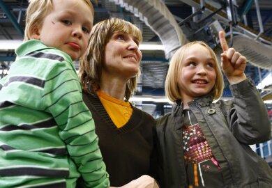 """Drei von 7500 Gästen: Simona Winkler aus Chemnitz mit ihrem Sohn Till (3) und Tochter Linda (7) waren dieses Jahr zum ersten Mal im Druckzentrum und beeindruckt """"von der langen Schlange an der Decke""""."""