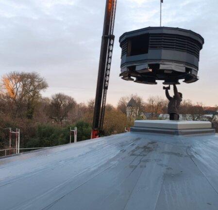 Mit einem Kran wurde die restaurierte Kuppel auf das Aquarium des Zoos in Leipzig gesetzt. Die Anlage wird zurzeit erneuert.