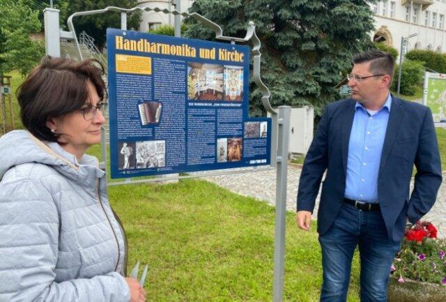 Xenia Brunner und Klingenthals Oberbürgermeister Thomas Hennig an der mit einem QR-Code versehenen Tafel am Marktplatz für den nun mehr-sprachig ausgestatteten Klingenthaler Rundweg.