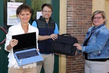 Antje Döbler (rechts), Finanzchefin im Rathaus von Grünhain-Beierfeld, übergibt die neuen Laptops an Schulleiterin Katrin Müller und Lehrer Patrik Sonntag.