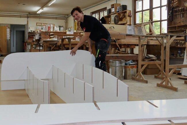 Tischlerin Konstanze Beyse steckt eines der formbaren Regale zusammen. Diese Möbelstücke kommen ohne Schrauben aus - nur an der Wand müssen sie befestigt werden.