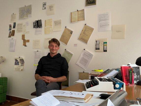 Felix Forsbach hat sich während seiner Residenz als Künstler in Augustusburg mit der NS-Vergangenheit der Kleinstadt befasst. Ein vormals leer stehendes Ladengeschäft an der Unteren Schlossstraße ist sein Projektraum. Hinter ihm an der Wand hängen einige seiner Rechercheergebnisse.