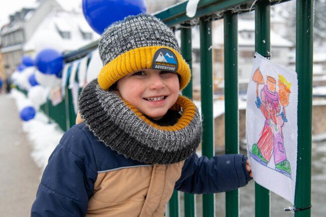 Der fast fünfjährige Oscar Lieven zeigt stolz sein Bild, das beim Lauf an der geschmückten Muldenbrücke in Penig zu sehen war.