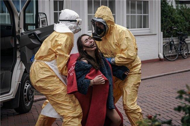 """Szene aus der ZDF-Neo-Serie """"Sløborn"""": Evelin Kern (Emily Kusche) wird von zwei Sanitätern in Schutzanzügen abtransportiert."""