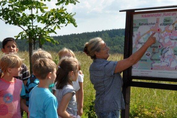 """<p class=""""artikelinhalt"""">Beate Müller (rechts) ist eine der drei Kräuterpädagoginnen, die regelmäßig mit interessierten Wanderern auf dem Kräuterlehrpfad unterwegs sind. Hier mit Kindern aus der Grundschule Rothenkirchen.</p>"""