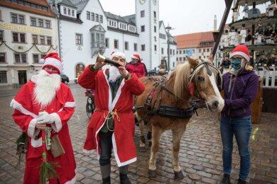 Karl-Heinz Dahle (links) und Christian Geißler sorgten als Weihnachtsmänner für ein bisschen Freude in Freiberg. Mit dabei: Pferd Maika und Gehilfin Klara Börner.
