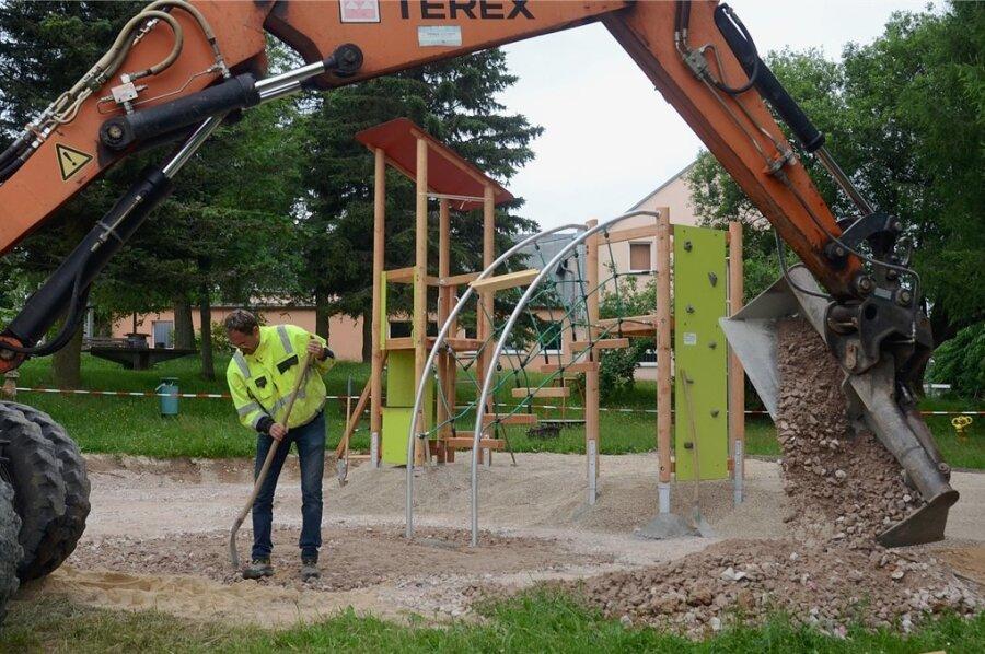 Bauunternehmer Heiko Wolf bereitet den Untergrund und installiert das neue Spielplatzgerät hinter dem Kulturhaus Beerheide.
