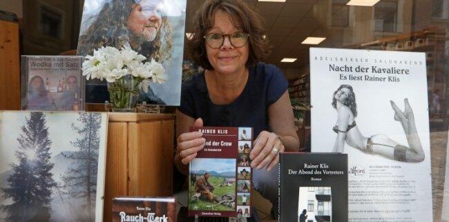 Andrea Jakob hinter dem Schaufenster der Buchhandlung, das sie aus Anlass seines Geburtstages mit Fotos und Werken von Rainer Klis gestaltet hat.