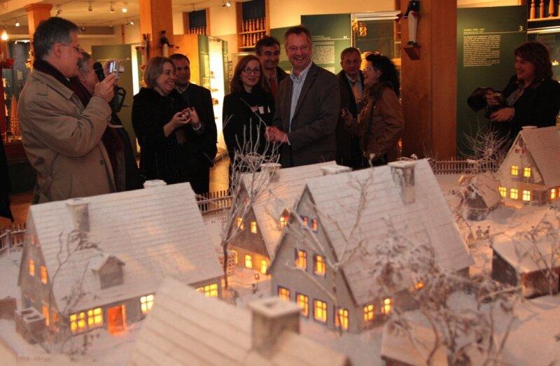 """<p class=""""artikelinhalt"""">Die Delegation aus Bulgarien besuchte unter anderem das Spielzeugmuseum, wo ihnen Tino Günther (Mitte) seinen Heimatort anhand des verschneiten Modelldorfes näher vorstellte. </p>"""