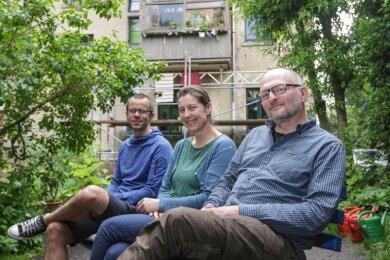 """René Härtel (von links), Jana Pöttrich und Jörg Lenk sitzen im Garten der """"Alten Cäcilie"""". Gemeinsam mit den anderen Bewohnerinnen und Bewohnern des Hauses haben sie eine Genossenschaft gegründet und das Gebäude übernommen. Bald stehen Renovierungsarbeiten an."""