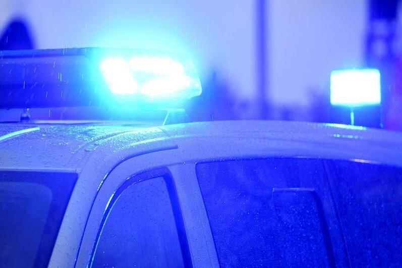 Blaulichter leuchten auf demDach eines Polizeifahrzeugs.