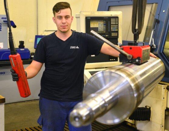 Erik Müller holt eine Walze aus der CNC-Maschine. Die Sächsische Walzengravur Frankenberg bildet junge Menschen zu Zerspanungsmechanikern aus.