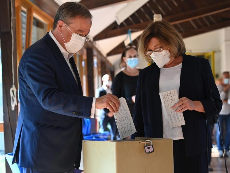 Falsch gefaltet: Armin Laschet und seine Frau Susanne stecken ihre Wahlscheine in die Urne.