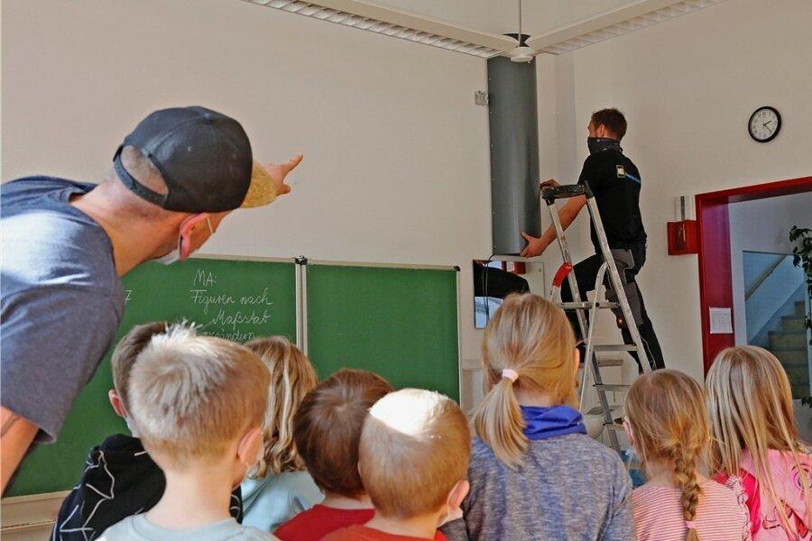 Nico Namyslak, Mitarbeiter der Firma Heinrich Schmidt, beim Montieren der Entkeimungsgeräte in der Grundschule im Ortsteil Weißbach. Das lassen sich Hortleiter Tim Fenzke und die Erstklässler nicht entgehen.