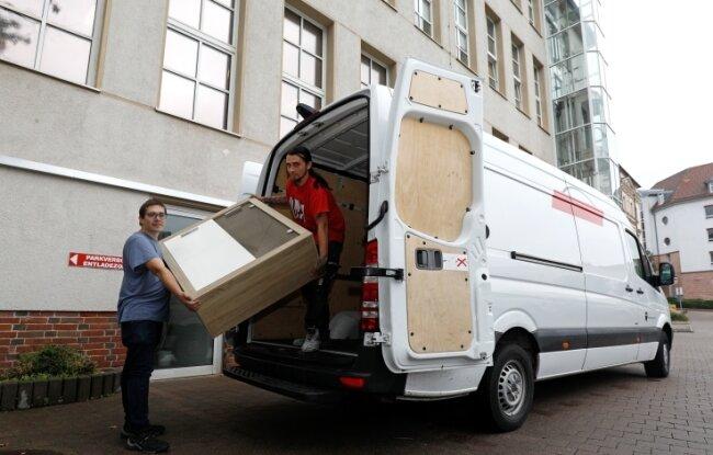 Andreas Schneider (l.) und Daniel Cyraick entladen Möbel an der Stadtpassage. Im alten Sparmarkt zieht wieder ein Geschäft ein.