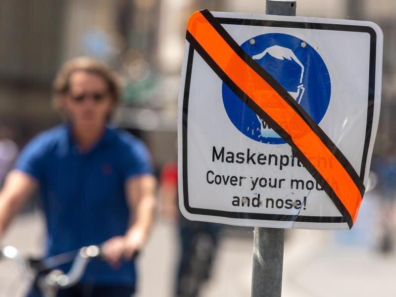 Ein mit orangen Klebeband durchgestrichenes Schild steht in der Münchner Innenstadt am Straßenrand. Die weitgehende Aufhebung der Maskenpflicht in Dänemark befeuert auch in Deutschland die Diskussion über den Sinn des Mund-Nasen-Schutzes.