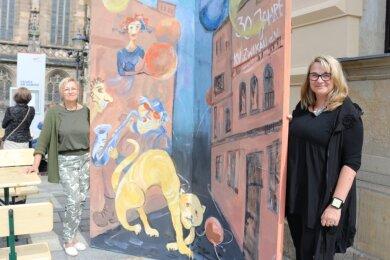 """Zwickauer Künstlerinnen Petra Jäntsch (l.) und Evelyn Loew haben den Aufsteller bemalt, der in der Galerie am Domhof noch bis zum 19. September auf den """"Sommersalon 2021"""" hinweist."""