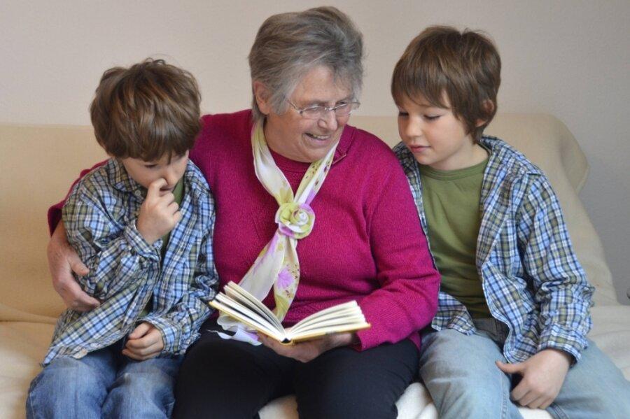 Kindern eine Geschichte vorzulesen, wie hier im Symbolbild die ältere Dame diesen Zwillingen - auch das gehört zu den Aufgaben eines Familienpaten.