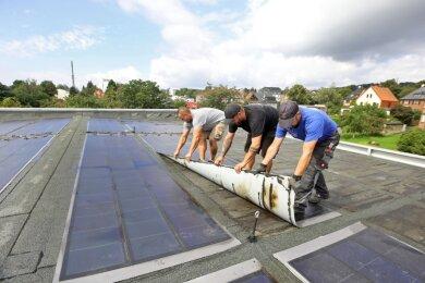 Mit purer Muskelkraft, aber vorsichtig lösen die Dachdecker die aufgeklebten Fotovoltaiksegmente von der Oberfläche des HOT-Badeland-Daches. Das hat Risse bekommen, durch die Wasser in großen Mengen eindringen konnte.