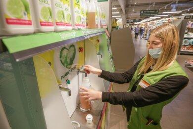 Globus-Mitarbeiterin Johanna Lange füllt an einer Station für Spülmittel wieder auf. Mit dem Nachfüllgerät will die Chemnitzer Filiale zum Einsparen von Plastikmüll beitragen.