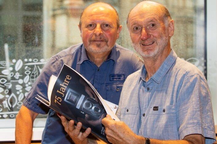 Clubchef Jürgen Zorn (rechts) und sein Vize Bernd Hegner blättern in der druckfrischen Broschüre, die sich der Fotoclub Vogtland zu seinem Jubiläum gegönnt hat.