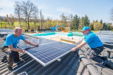 Mirko Kretzschmann (links) von der Firma Badbetreiber Erzgebirge und Knut Hartmann, Inhaber der Firma HFS Hartmann aus Ehrenfriedersdorf, montieren die Photovoltaikanlage auf dem Jahnsdorfer Freibaddach.