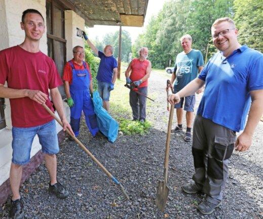 Steve Ittershagen (r.) und die Mitglieder des Freiberger Modelleisenbahnclubs machen den Haltepunkt Zug sauber.