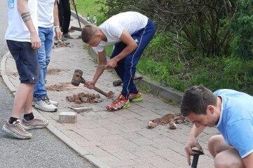 Mitglieder des Wechselburger Jugendclubs reparierten den Fußweg am Rathaus.