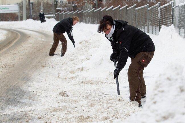 Mitarbeiterinnen des Helios Vogtland-Klinikums halten den Gehweg an der Röntgenstraße frei - wenn nicht gerade der Schneepflug alles wieder auf den Fußweg zurück befördert. Dann geht alles von vorn los.