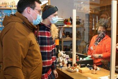 Franziska und Celvin Kotsch (l.) aus Annaberg-Buchholz kauften am Mittwoch letzte Geschenke in der Annaberger Kunststube bei Ina Döring (r.) ein.