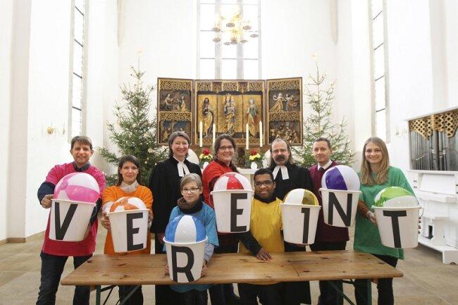 """Die Gemeindepädagogen machten die Fusion anschaulich, indem sie sich und den Anwesenden farbige Bälle zuspielten und diese im Altarraum mit der Beschriftung """"vereint"""" präsentierten."""
